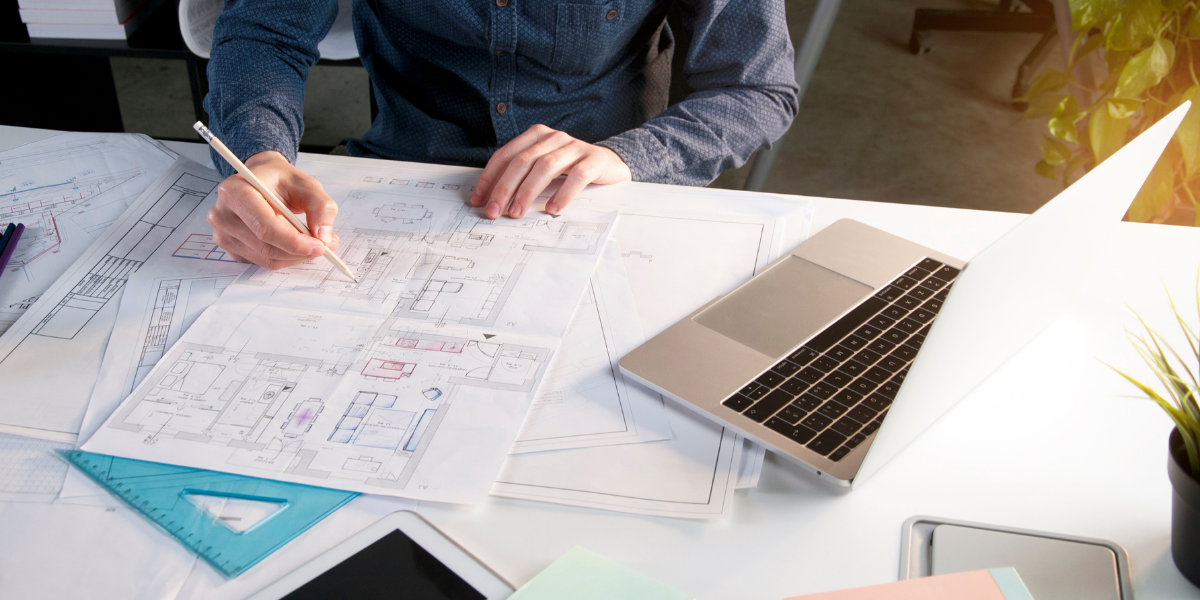 Someone working on blueprints with laptop on desk