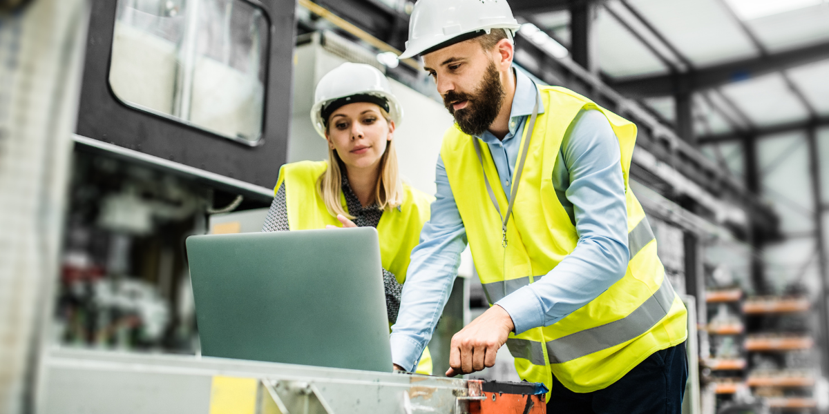 People with Hard hats in a warehouse looking at a laptop